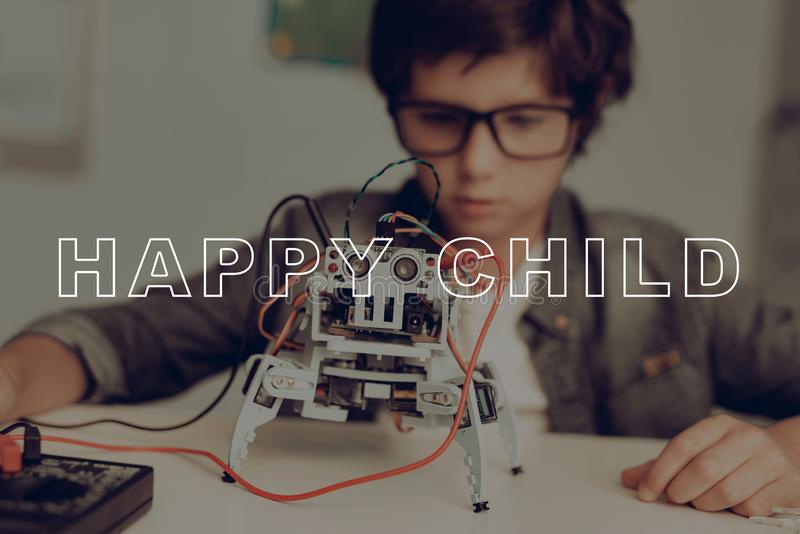 Smart Little Kid In Glasses Is Creating A Robot. stock photos