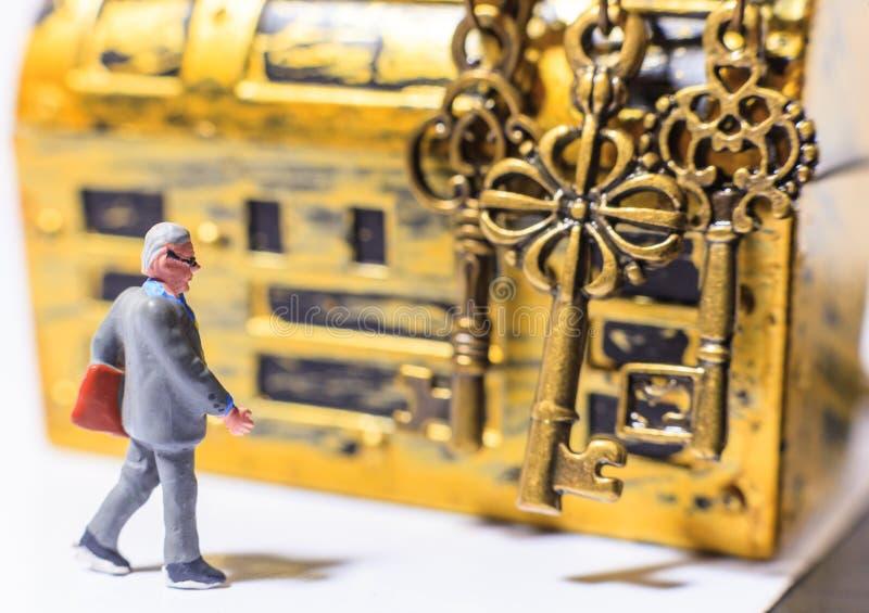 Smart lyckad expert för affärsmaninvesteringguru som väljer guld- framgångtangenter för att öppna den guld- skattbröstkorgen för  royaltyfria bilder