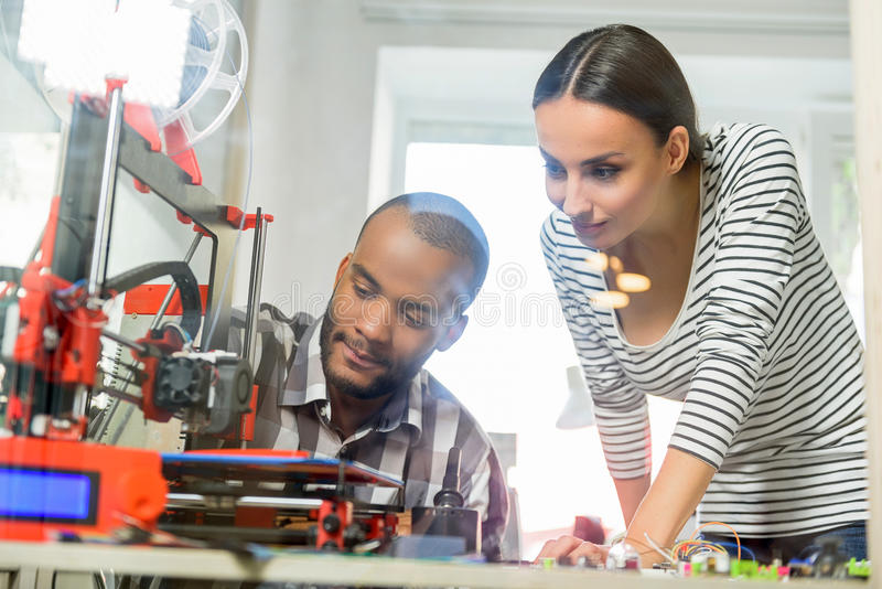 Smart man and woman watching 3d printing stock photos