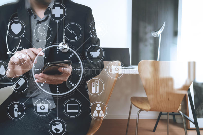 Smart medical doctor working with smart phone and digital tablet. And laptop computer on dark wooden desk in modern office with virtual icon diagram stock photos