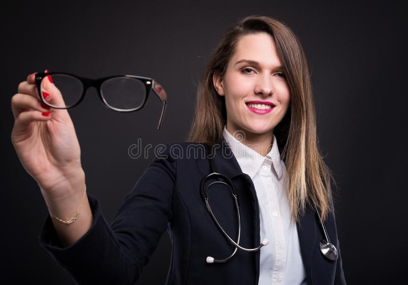 Smart medical female with glasses and stethoscope. Isolated on dark studio backgroundund royalty free stock photos