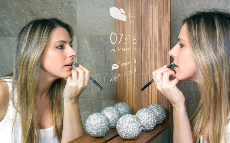 Smart mirror concept. Young woman applying lip liner in front of a smart mirror that gives information royalty free stock photo