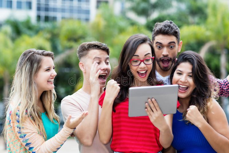 Smart nerdy french female student with tablet computer and group of cheering students royalty free stock image