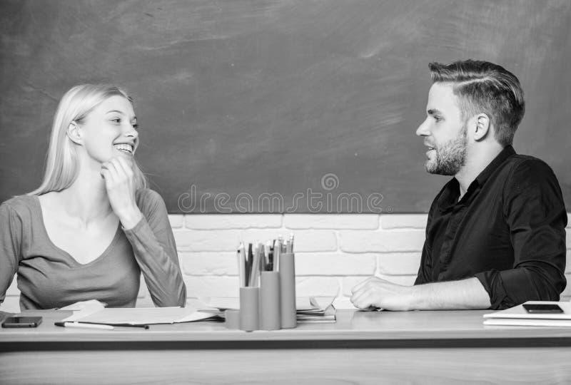 Smart och s?kert L?rare och l?rare som sitter p? skrivbordet Stilig man och n?tt kvinna tillbaka till skola universitetar royaltyfria foton