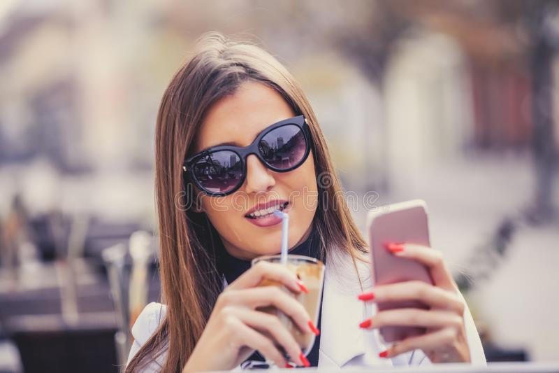 Smart Phone allegro della tenuta della giovane donna e choco caldo bevente fotografia stock