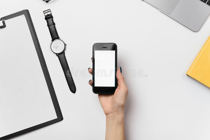 Smart phone with blank copy space screen in female hand. Flat lay white office desk with supplies, top view workspace royalty free stock image