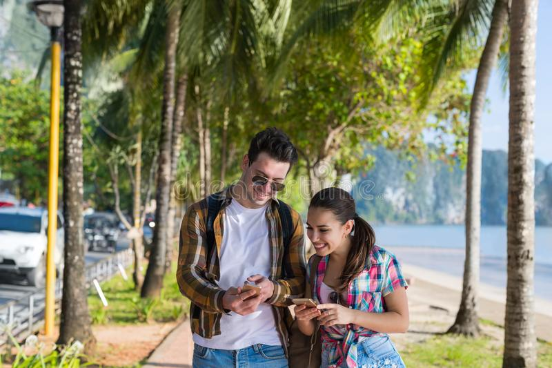 Smart Phone casuali delle cellule di uso delle coppie nel parco tropicale delle palme, bei giovani sorridenti felici che chiacchi immagine stock libera da diritti