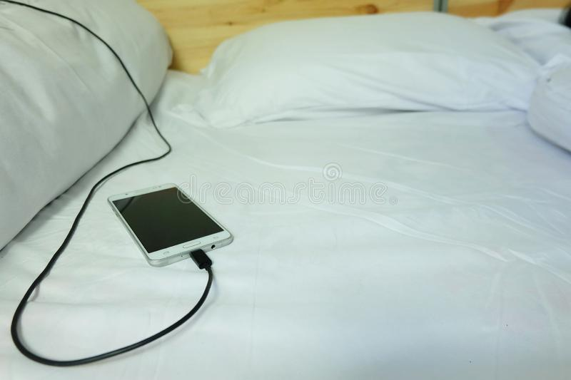 Smart phone is charging is plugged on the white bed royalty free stock images
