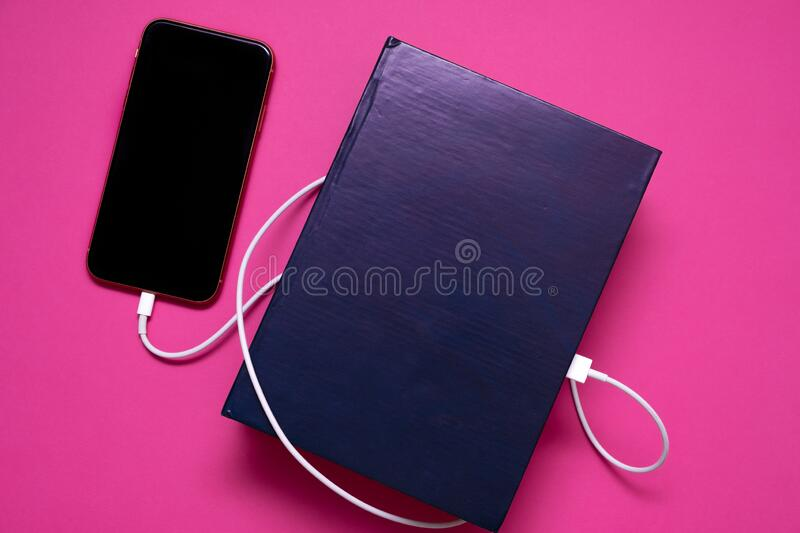 Smart phone connected to the old book with a cable, and download information from there royalty free stock photography