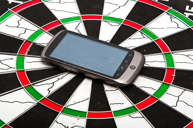 Smart phone on dartboard. Modern mobile smart phone covering center of dartboard stock photo