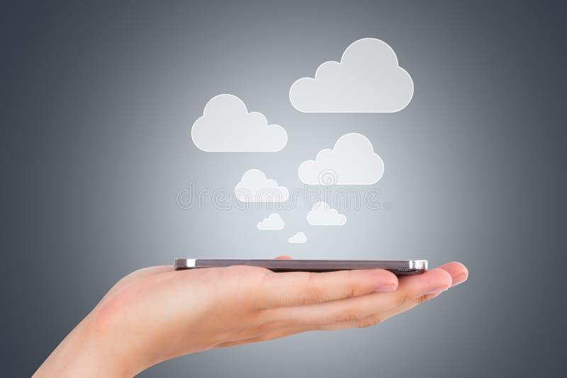 Smart Phone della tenuta della mano con le icone della nuvola fotografie stock libere da diritti