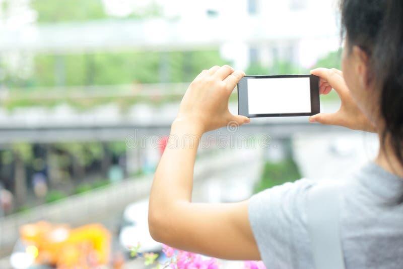 Smart Phone della tenuta delle mani in città moderna fotografia stock