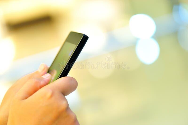 Smart Phone della tenuta delle mani in città moderna fotografia stock libera da diritti