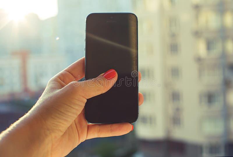 Smart Phone della tenuta delle mani della donna in città fotografie stock libere da diritti