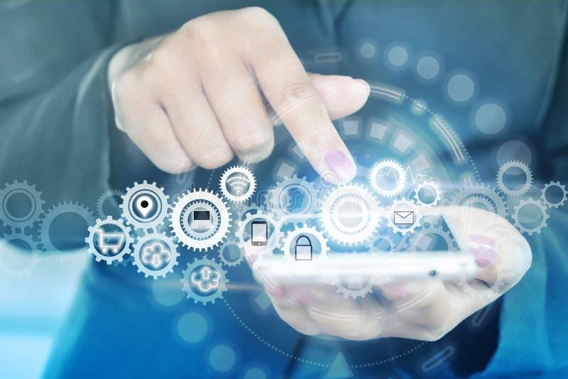 Smart Phone della tenuta della mano della donna con l'icona degli ingranaggi, concetto della regolazione di tecnologia immagini stock libere da diritti