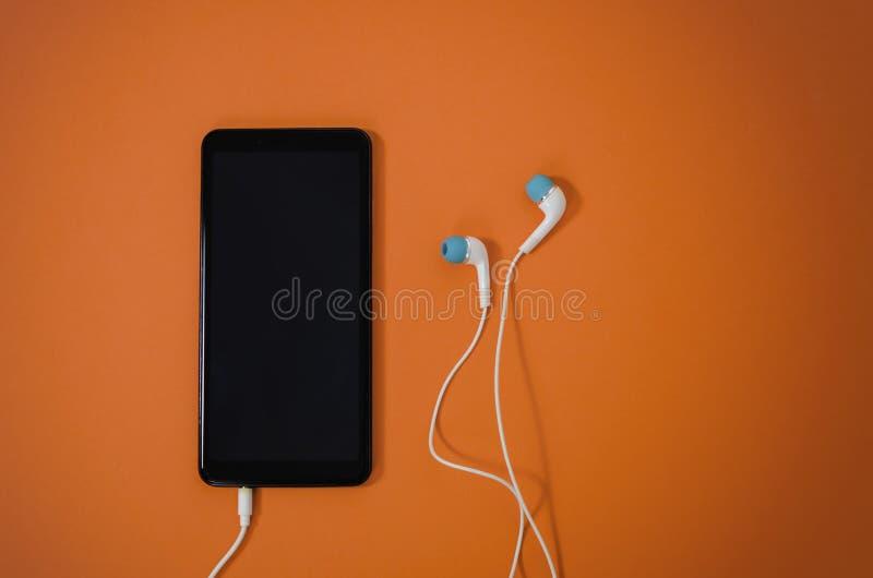 Smart phone and earphones on orange background royalty free stock photo