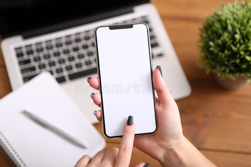 Smart phone in hand on the background of working business environment, empty screen stock photography