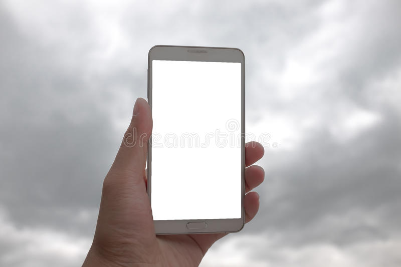 Smart phone in hand on cloud background with copy space stock image