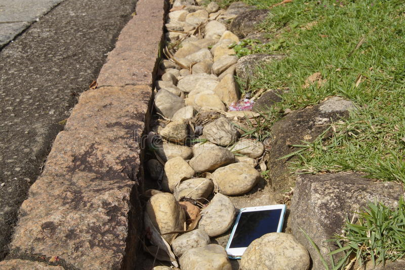 A smart phone lost alongside of a road. An electronic device lost among stones alongside of a flat-rocky path in a bright day stock image