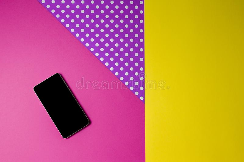 Smart phone lying on colorful background, top view. royalty free stock photography