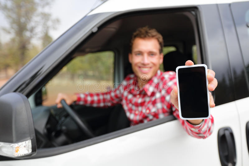 Smart phone man in car driving showing smartphone. Display smiling happy. Male driver using apps showing blank empty screen sitting in drivers seat. Focus on stock photos
