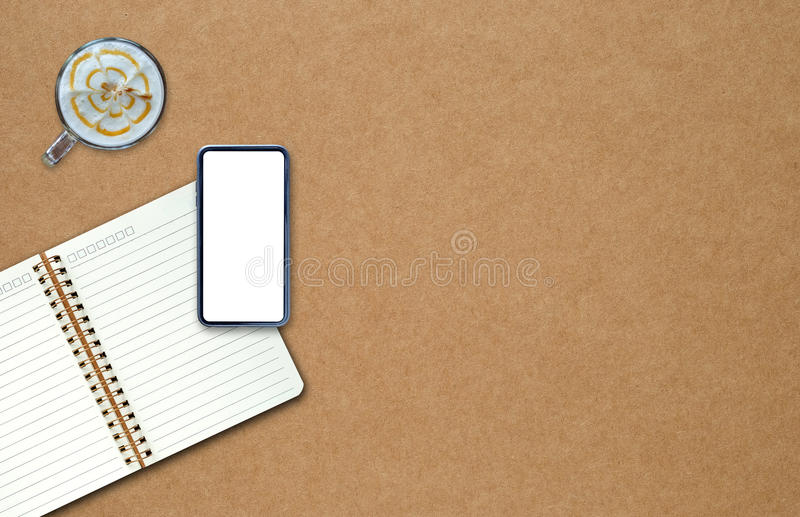 Smart phone on notebook with coffee on brown paper. Smart phone on notebook with coffee on brown paper background stock photography