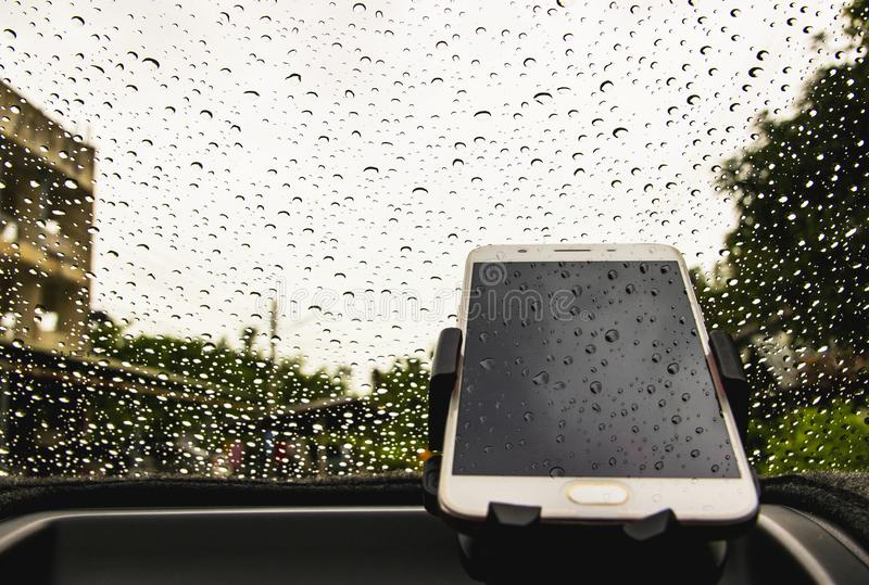 Smart phone is off line with raindrops background on the mirror in the car. Smart phone is off line on front of the car with raindrops background stock photo