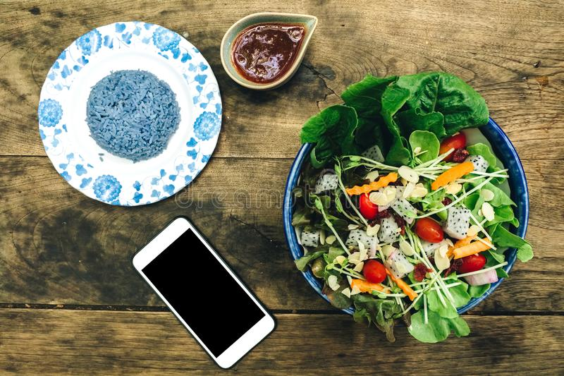 Smart phone with salad and blue rice. North thailand dish royalty free stock photo