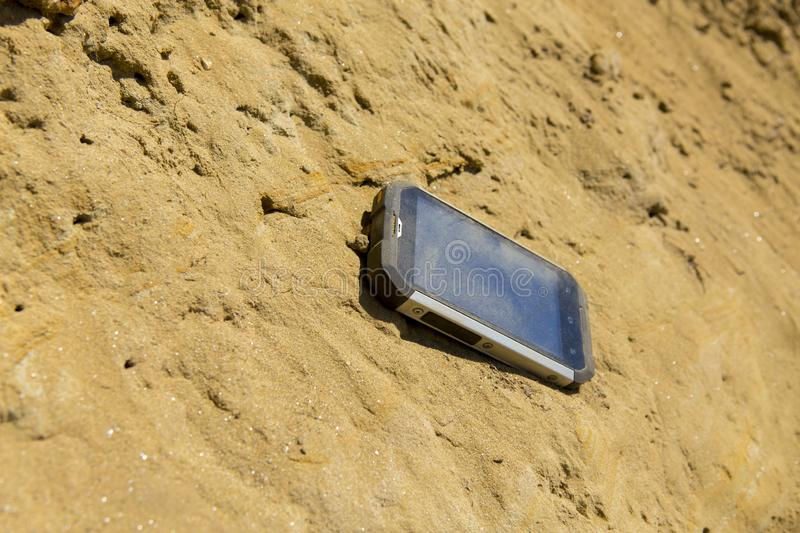 Smart phone in sand for commercial photo stock images