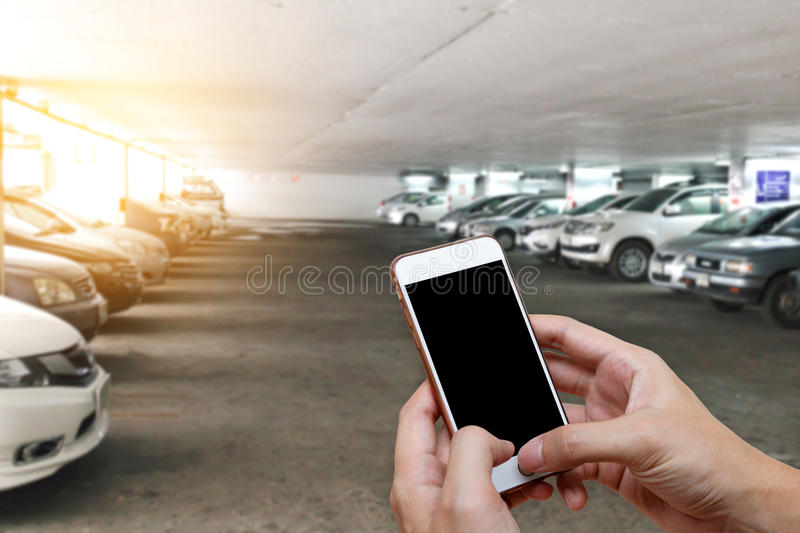 Smart phone showing blank screen in man hand with blur cars park royalty free stock photography