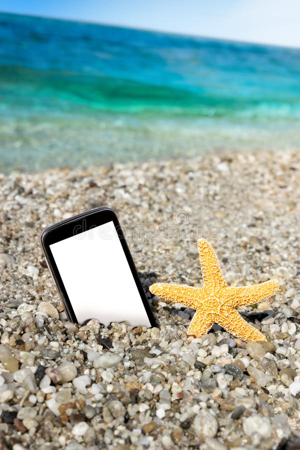 Smart phone and starfish with wavy sea. On blurry background stock photos