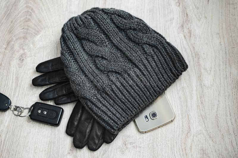 Smart phone with winter hat, black leather gloves and remote control for car stock photography