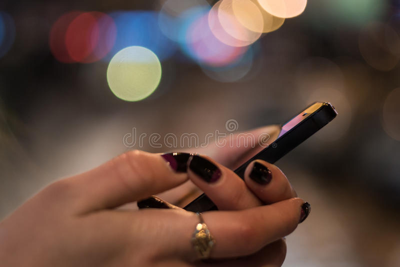 Smart phone in woman hands in front of blurred city lights royalty free stock photography