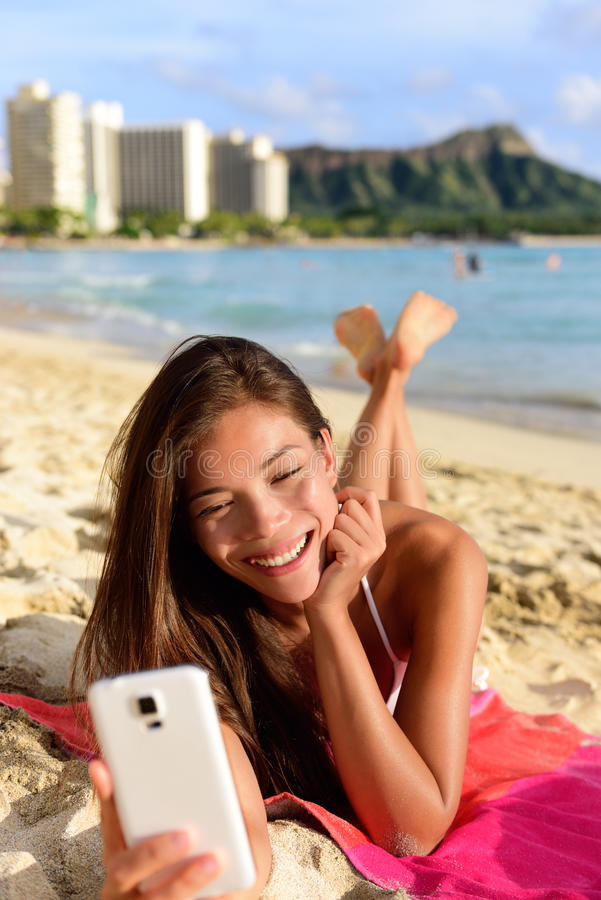 Smart phone woman using smartphone app on beach. Smiling laughing having fun. Girl reading or messaging or browsing on internet smiling happy outdoors. Mixed royalty free stock images