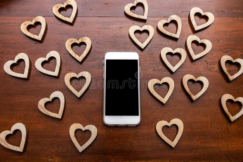 Smart phone and wooden heart shapes on wooden desk. For when you truly love your mobile device stock images