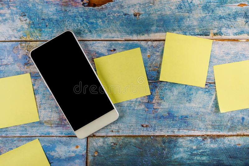 Yellow sticky notes empty square reminder with smart phone in the blue old wooden background. Smart phone with yellow sticky empty square notes reminder in the royalty free stock photos