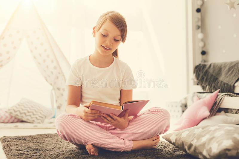 Smart pleasant girl reading an interesting story. Favourite hobby. Smart nice pleasant girl sitting on the bed and holding a book while reading an interesting royalty free stock photos