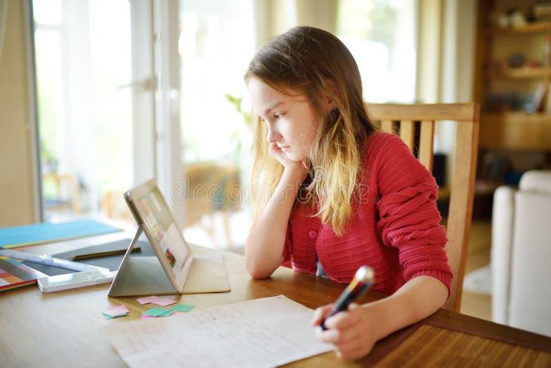 Smart preteen schoolmeisje die haar thuiswerk met digitale tablet thuis doen Kind die gadgets gebruiken aan studie royalty-vrije stock foto