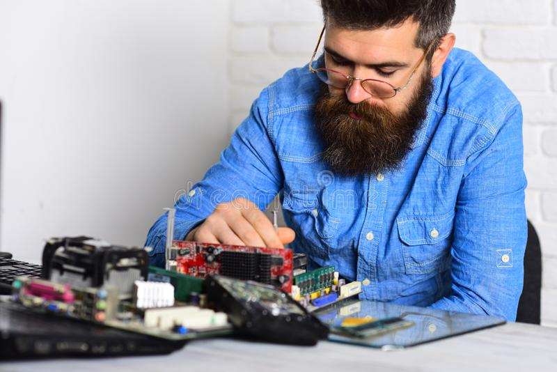 Smart professional. Bearded man repair circuit board. Engineer or technician at work. Bearded hipster works on fixing stock image