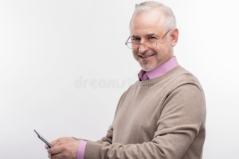 Smart dark-eyed elderly university professor using his smart phone royalty free stock images