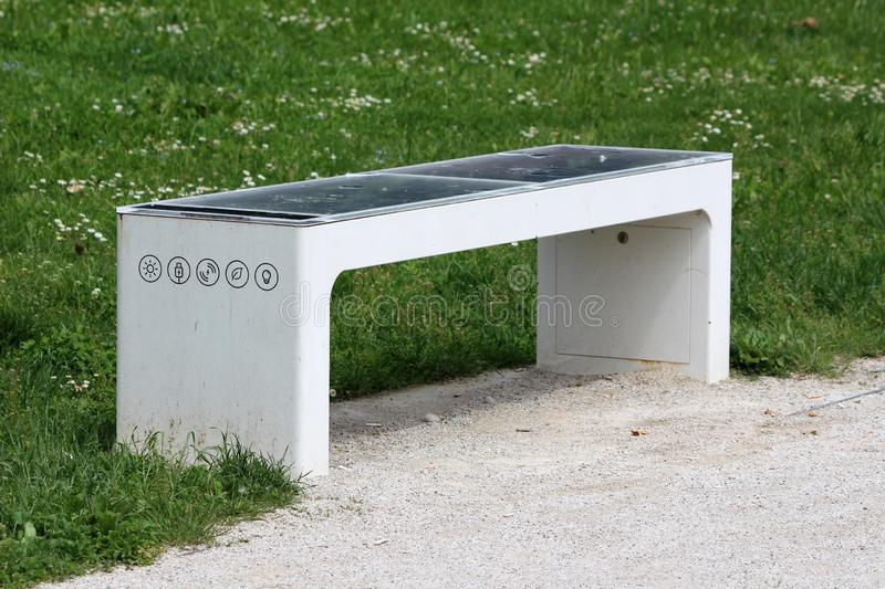 Smart public park bench with destroyed solar panel used to power battery used for charging mobile phones and lightning gravel path royalty free stock photo
