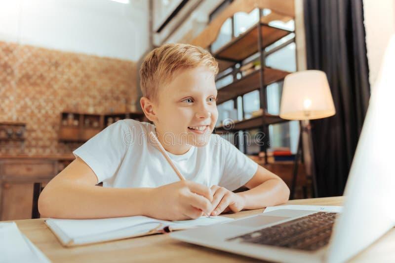 Joyful nice boy doing his home task. Smart pupil. Joyful nice positive boy sitting in front of the laptop and writing while doing his home task royalty free stock photography