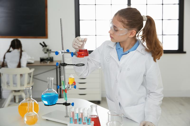 Smart pupil making experiment in class stock photo