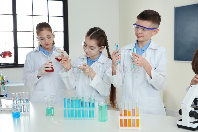 Pupils making experiment in chemistry class stock image