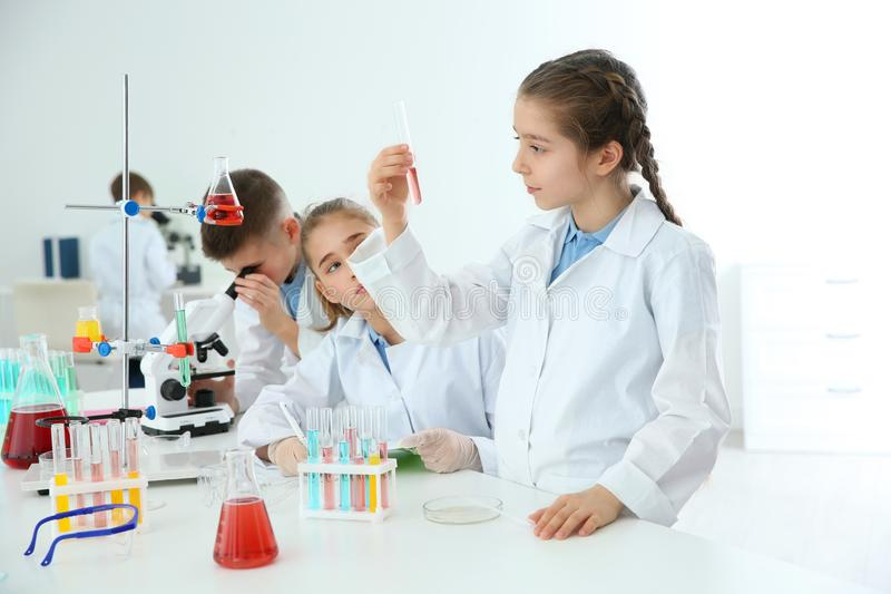 Smart pupils making experiment at table in class stock photos