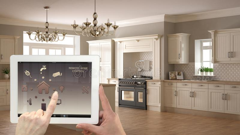 Smart remote home control system on a digital tablet. Device with app icons. Interior of classic white and wooden kitchen in the b. Ackground, architecture royalty free stock photos