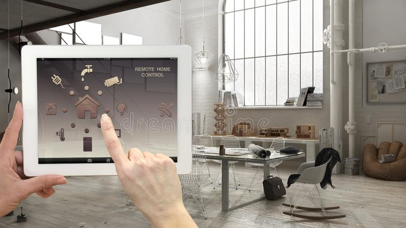 Smart remote home control system on a digital tablet. Device with app icons. Interior of industrial office in the background, arch stock photo
