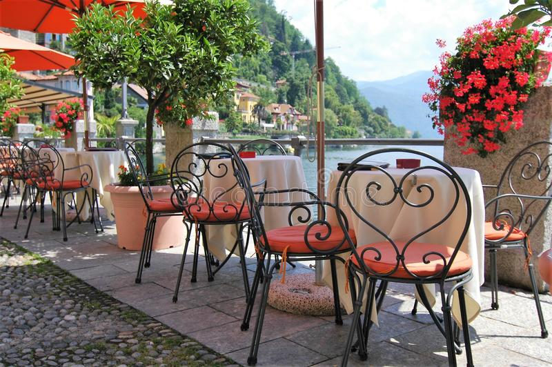 Smart restaurang med tabeller och stolar som förbiser den italienska sjön fotografering för bildbyråer
