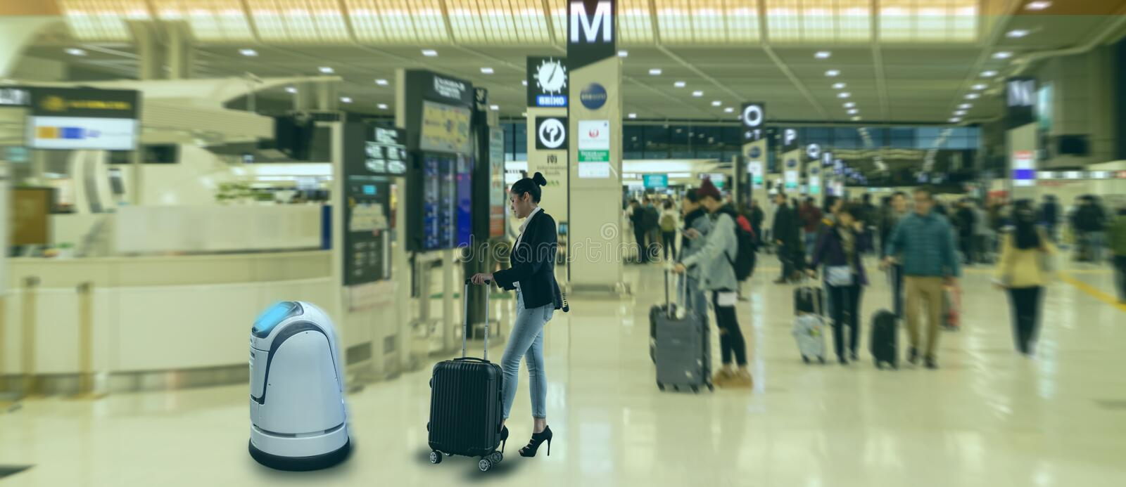 Smart robotic technology concept, The passenger follow a service robot to a counter check in in airport, the robot can help and gi stock photography
