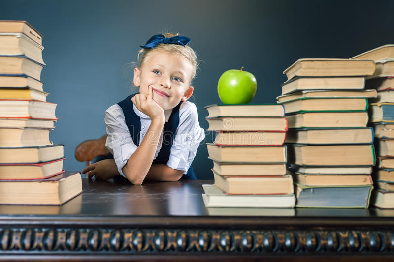 Smart school girl sitting at the table with many books stock images